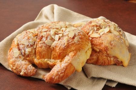 Two golden custard filled almond croissants