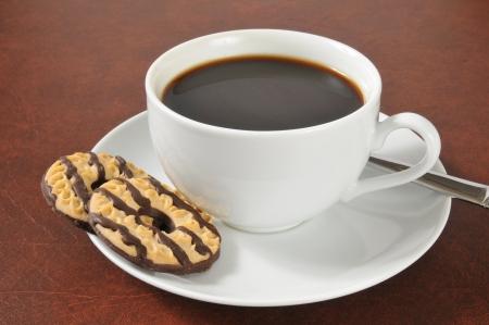 Een kopje zwarte koffie met fudge gestreepte zandkoekjes Stockfoto