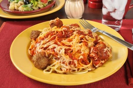 Spaghetti and meatballs with a mediterranean salad Фото со стока