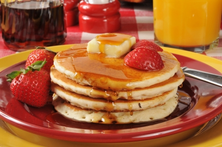A stack of hot cakes with syrup and strawberries
