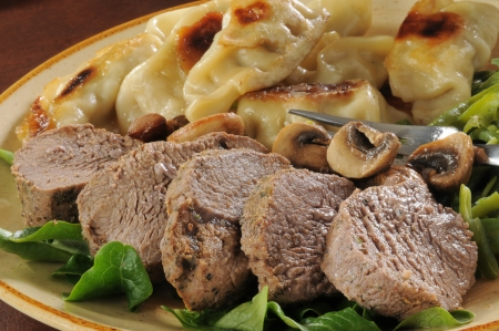 Juicy roast beef with potstickers and green beans photo