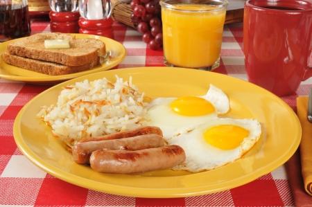 hash browns: Salsiccia e uova con patate fritte e toast Archivio Fotografico