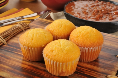 cornbread: Corn bread muffins with a cast iron skillet of chili con carne in the background Stock Photo