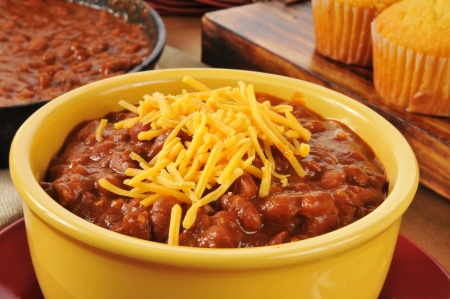 A bowl of chili con carne with shredded cheddar cheese