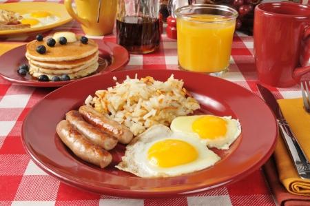 papas doradas: Salchicha y huevo del desayuno con panqueques de arándanos Foto de archivo