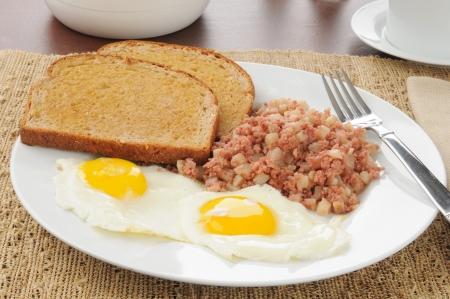 papas doradas: desayuno de corned beef hash y huevos con tostadas