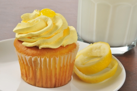 A lemon cupcake and a glass of milk