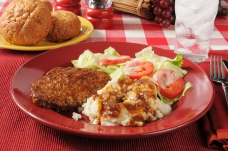 A plate of meatloaf with mashed potatoes and gravy with a salad photo