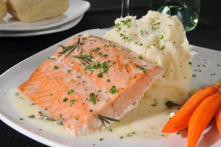 Closeup of a plate of baked salmon with carrots and mashed potatoes with country gravy photo