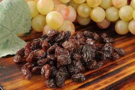 Fresh sun dried raisins with a bunch of grapes