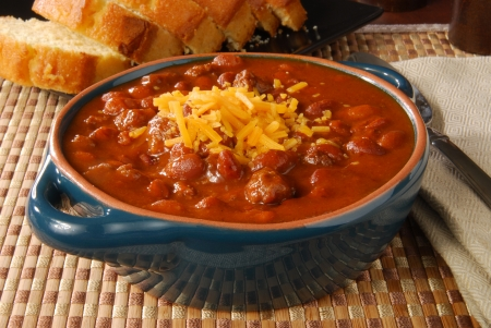 A bowl of hot chili con carne topped with cheddar cheese Reklamní fotografie
