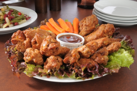 A party tray with chicken wings and carrot sticks, with a four ban salad in the background photo