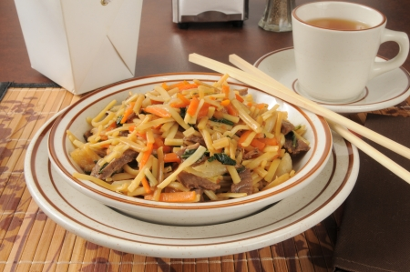 lo mein: A bowl of beef lo mein with a cup of tea
