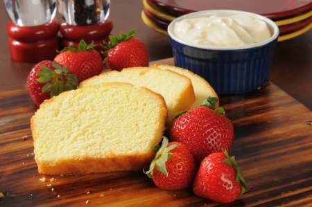 pound cake: Sliced pound cake, fresh strawberries and whipped cream on a cutting board