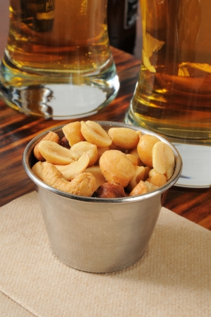 A tin of cashews on a bar counter with tall glasses of beer in the background