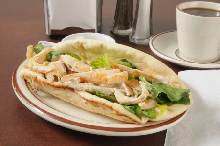A chicken sandwich with romain lettuce, won ton strips and Caesar dressing on flatbread