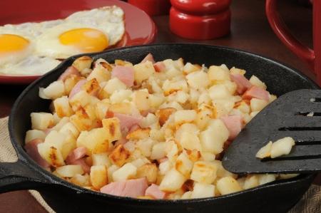 papas doradas: Hash browns estilo sure�o con jam�n y huevos en una sart�n de hierro fundido
