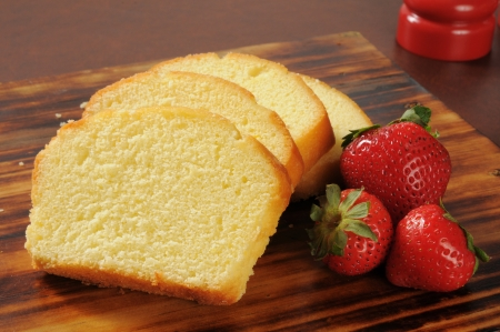 Slices of rich moist pound cake with fresh strawberries Stockfoto