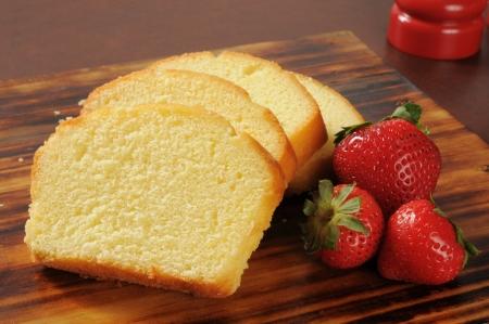 Slices of rich moist pound cake with fresh strawberries Standard-Bild