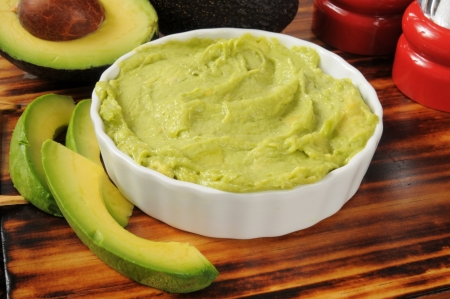 A bowl of fresh guacamole with fresh avocado Stock Photo