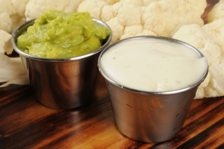 Closeup of silver dishes of ranch dip and guacamole with cauliflower