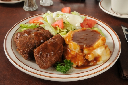 Meatloaf dinner with mashed potatoes and gravy with a green salad photo