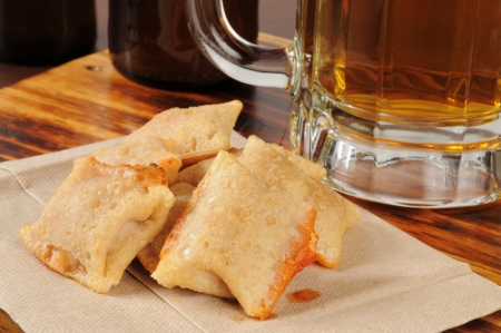 Pizza rolls on a napkin with a mug of cold beer in the background