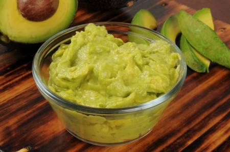 Fresh guacomole dip in a glass bowl with fresh avocado