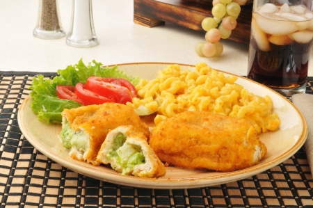 Chicken stuffed with broccoli, served with macaroni and cheese and a salad photo