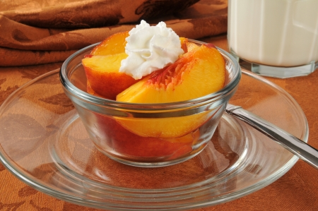 Sliced peaches with whipped cream and a glass of milk