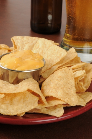 Closeup of tortilla chips with a glass of beer in the background Stock Photo