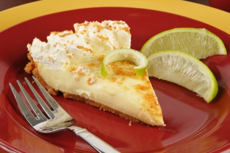 Closeup of key lime pie with fresh lime wedges