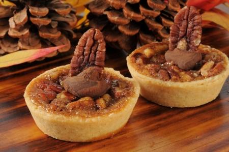 pecan pie: Pecan pie tartas de postre en una mesa de Acción de Gracias festivo con piñas y hojas de otoño