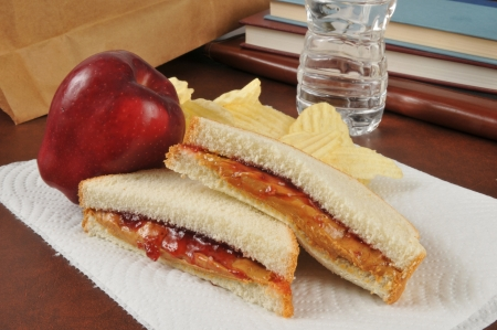 A peanut butter and strawberry jam sandwich with chips and an apple