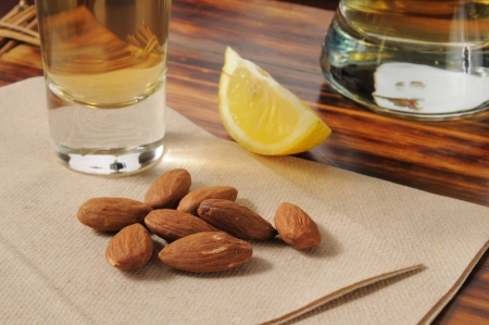 Roasted almonds on a bar napkin with a shot of tequila and beer photo