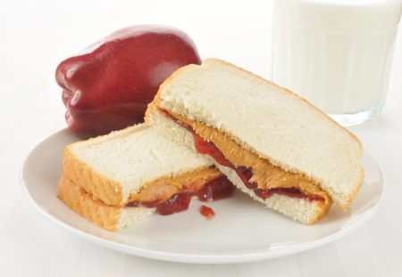 Pindakaas en aardbeienjam sandwich met een appel en een glas melk