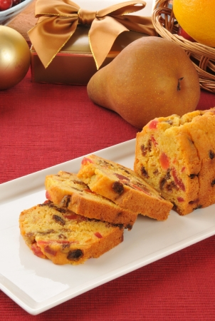 Sliced fruitcake on a table with Christmas gifts and decorations photo
