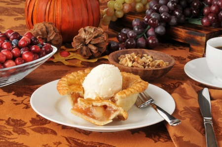 An individual serving of apple pie with ice cream on a holiday table