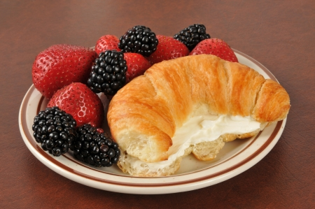 A golden croissant with cream cheese and fresh strawberries and blackberries Archivio Fotografico