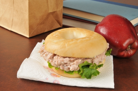 tunafish: A tunafish sandwich on a bagle with an apple and school books