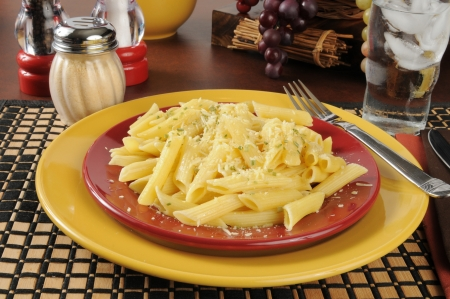 A plate of buttered penne rigate noodles topped with grated Parmesan and Romano cheeses