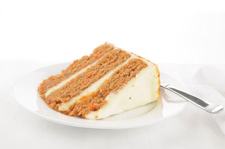 Een plak van gelaagde carrot cake op een hoge sleutel achtergrond Stockfoto