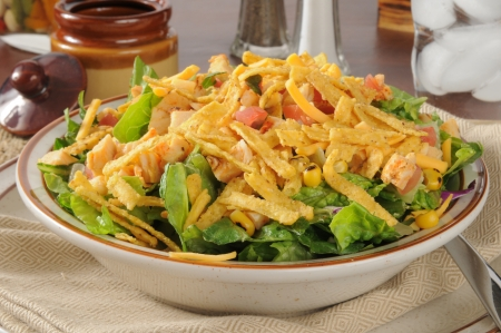 croutons: A bowl of taco salad with tortilla strips, chicken, corn, lettuce and tomatoes