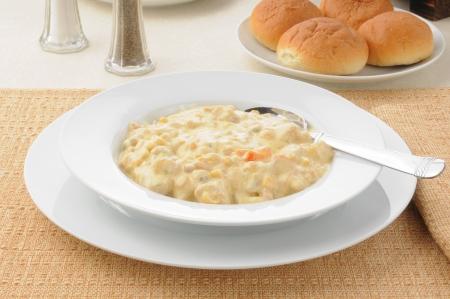 chowder: A bowl of corn chowder with dinner rolls