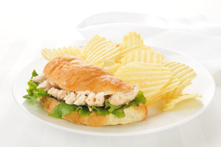 A chicken sandwich on a croissant with potato chips on a high key background Фото со стока - 22662109