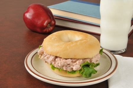 tunafish: A tuna sandwich on a bagel with an apple, glass of milk and school books