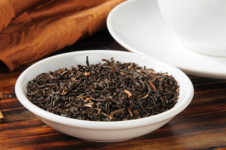 loose leaf: Suelta la hoja de t� negro en un plato de la muestra junto a una taza de t�