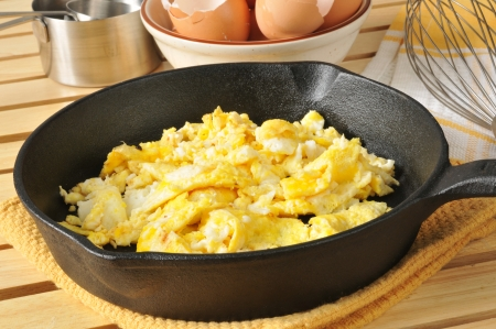Fresh cooked scrambled eggs in a cast iron skillet with brown egg shells in the background