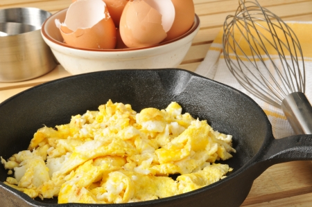 Scrambled eggs with brown egg shells in a bowl behind Stock Photo