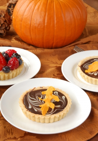 Chocolate and fruit dessert tarts on a buffet with a pumpkin and pine cones for Halloween photo